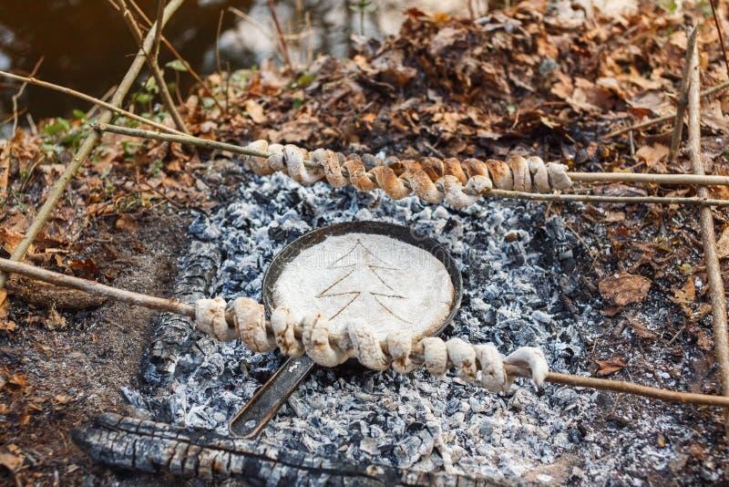 Cociamo il pane dalla pasta in una pentola sui carboni del fuoco fotografia stock