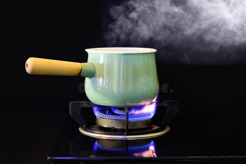 Cocido al vapor del agua al vapor del vintage del pote en estufa de gas de la llama imagenes de archivo