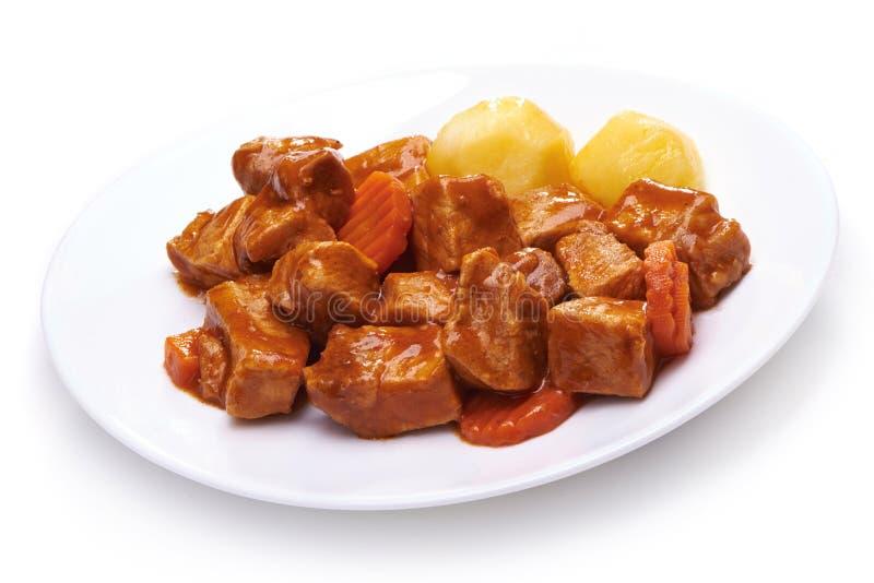 Cocido húngaro, caldo de buey con las patatas en el fondo blanco imagen de archivo