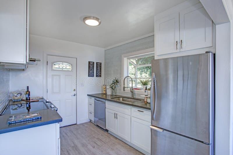 Cocina acogedora y pequeña con los gabinetes blancos imagenes de archivo