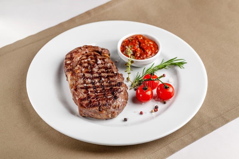 Cocina americana Filete de carne de vaca con la salsa de tomate del Bbq y los tomates de cereza rojos Un vidrio de vino fresco Pl fotos de archivo libres de regalías