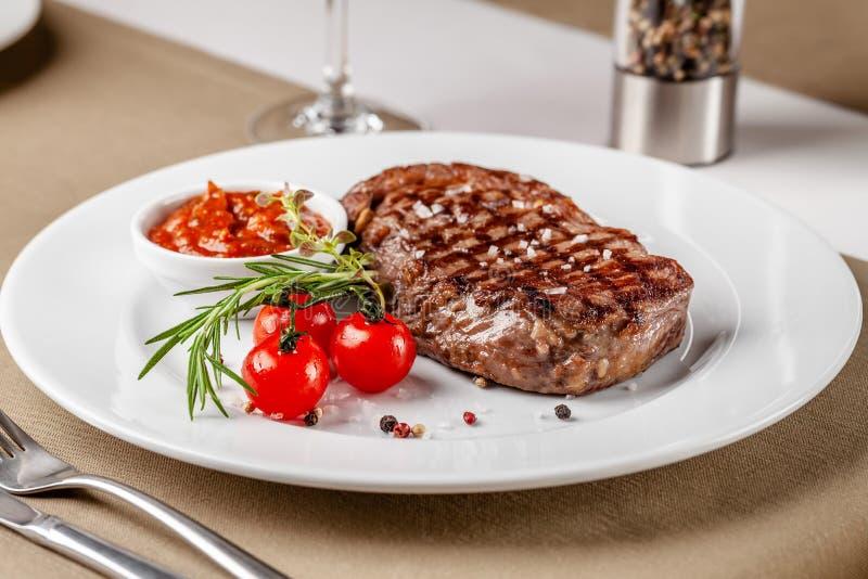 Cocina americana Filete de carne de vaca con la salsa de tomate del Bbq y los tomates de cereza rojos Un vidrio de vino fresco Pl fotografía de archivo