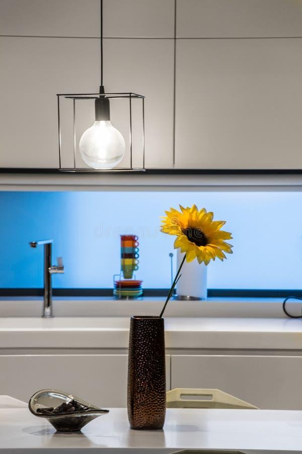 Cocina blanca del fondo con una flor amarilla imagen de archivo libre de regalías