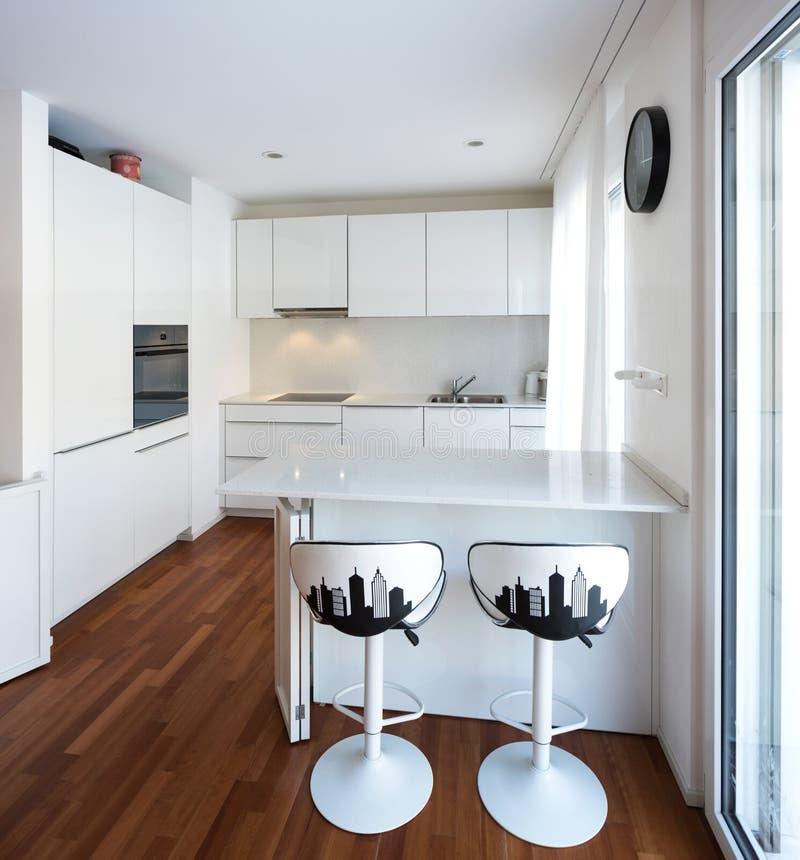 Cocina blanca moderna con la península foto de archivo
