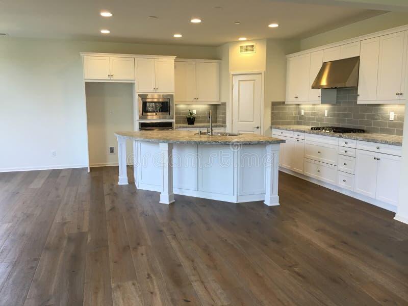 Cocina blanca moderna hermosa vacía con los pisos de madera imagen de archivo libre de regalías