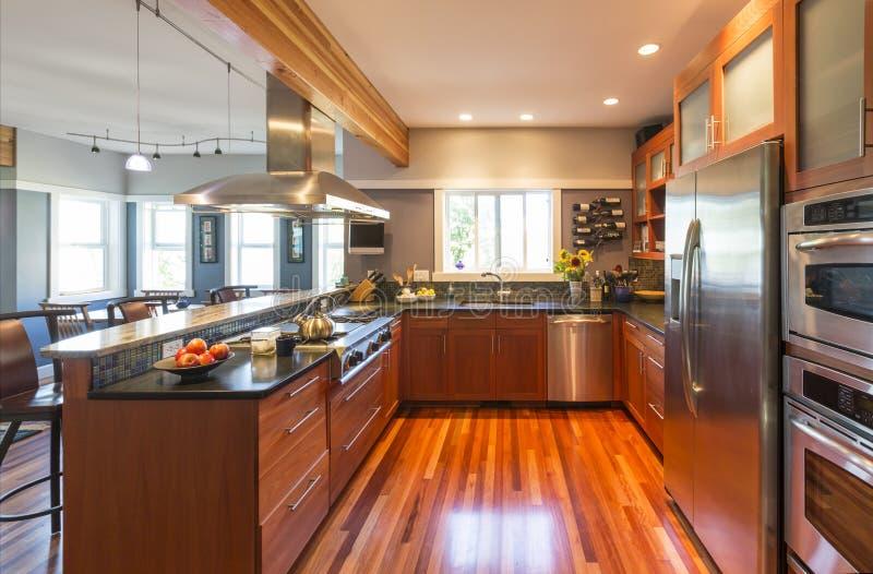 Cocina casera contemporánea de alta calidad con los gabinetes, el suelo de parqué, los dispositivos del acero inoxidable, las ven imágenes de archivo libres de regalías