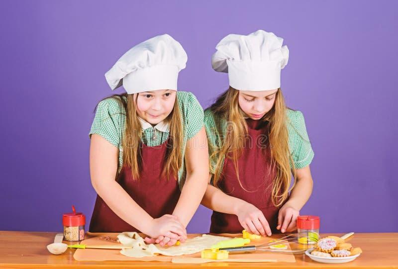 Cocina casera a su alma Niñas que preparan el alimento cocido casero Pequeños niños que cuecen en casa Cocineros adorables fotos de archivo libres de regalías