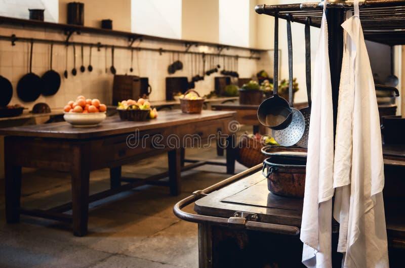 Cocina centenaria de la antigüedad XIX con los ingredientes de las herramientas, de las cacerolas, del pote y alimentarios foto de archivo libre de regalías