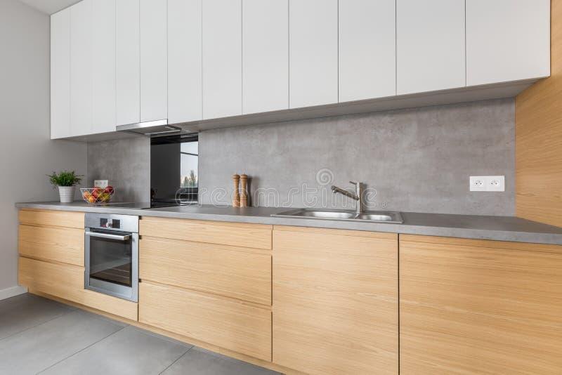 Cocina con el worktop concreto y los muebles de madera fotografía de archivo