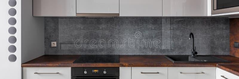 Cocina con el worktop del granito y el backsplash concreto imagenes de archivo