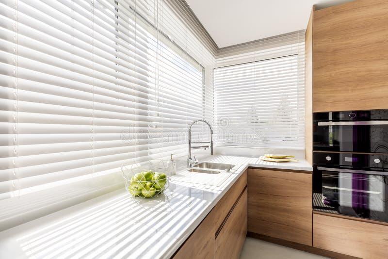 Cocina con las persianas de ventana blancas imagenes de archivo