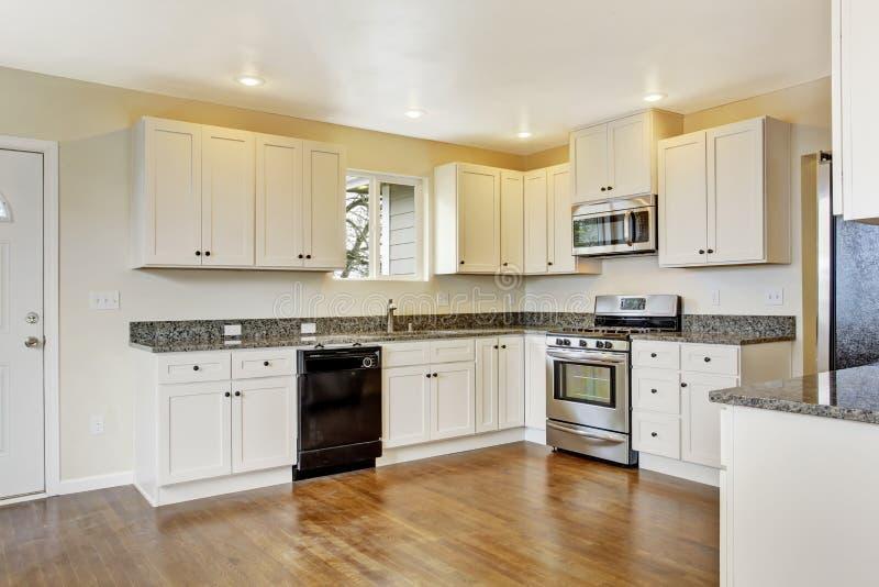 Cocina con los gabinetes y los tops blancos del granito for Cocinas con gabinetes blancos