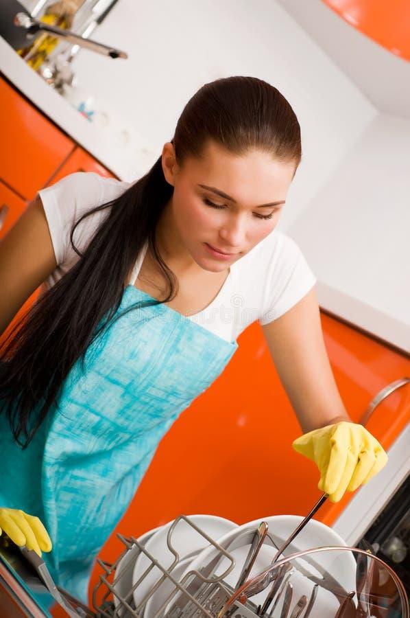 Cocina de la limpieza de la mujer usando la lavadora del plato fotografía de archivo