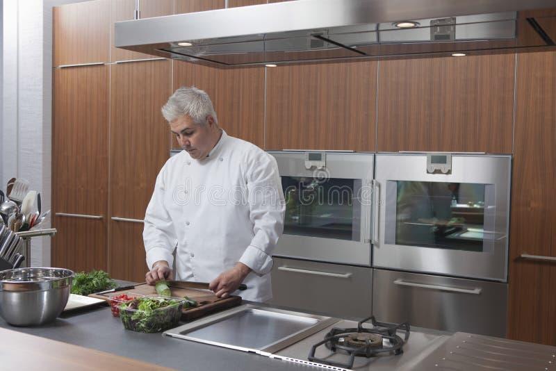 Cocina del anuncio publicitario de Chopping Vegetables In del cocinero fotos de archivo