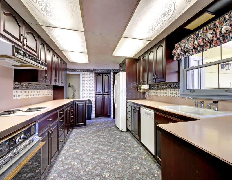 Cocina estrecha de madera vieja con la alfombra y las cortinas. imagenes de archivo
