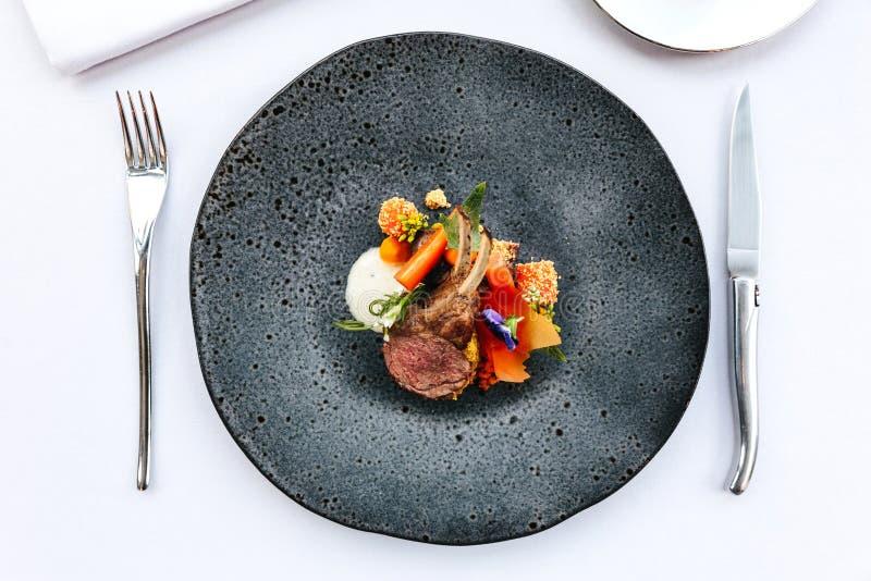 Cocina francesa moderna: El cuello y el estante asados del cordero sirvieron con la zanahoria, el curry amarillo servido en placa imagen de archivo