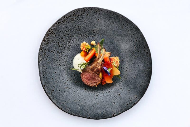Cocina francesa moderna: El cuello y el estante asados del cordero sirvieron con la zanahoria, curry amarillo servido en placa de imagen de archivo libre de regalías