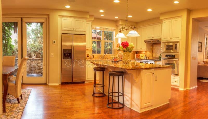Cocina grande con la iluminación ahuecada, pisos de madera foto de archivo