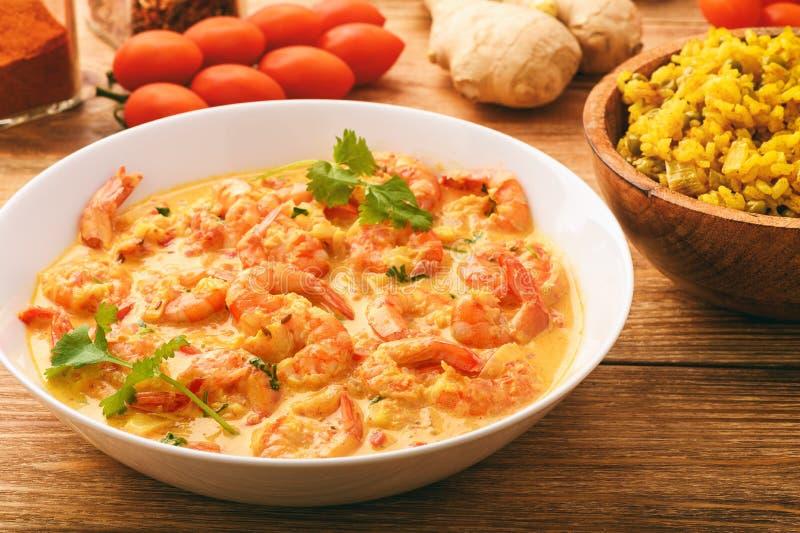 Cocina india - camarones en salsa y arroz del jengibre con curry y el guisante verde imagenes de archivo