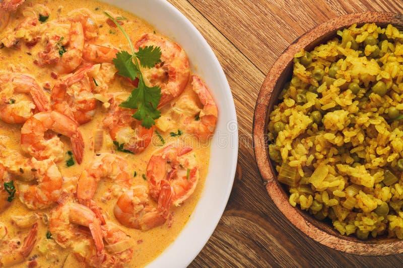 Cocina india - camarones en salsa y arroz del jengibre con curry y el guisante verde foto de archivo libre de regalías