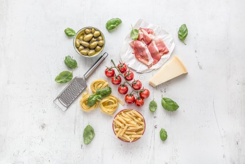 Cocina italiana o mediterránea e ingredientes de la comida en la tabla concreta blanca Tomates del aceite de oliva de las aceitun fotografía de archivo libre de regalías