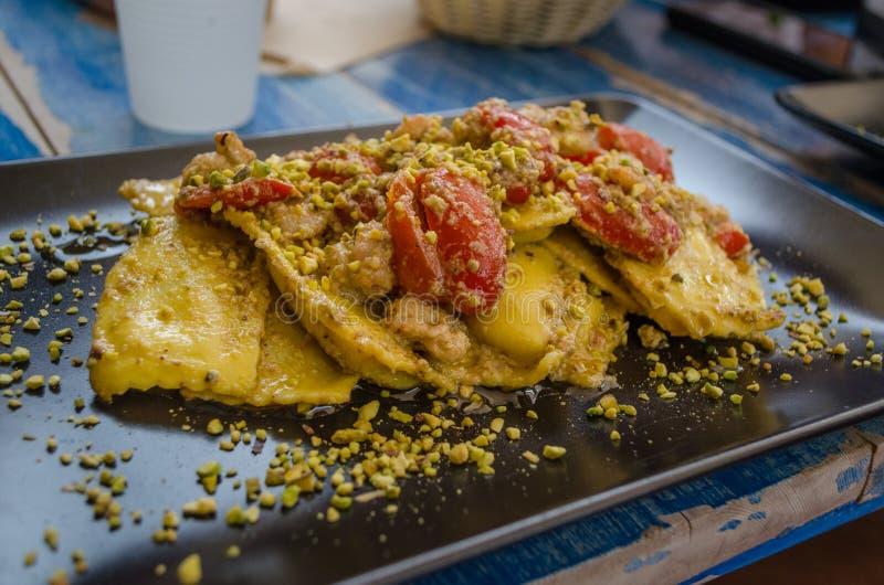 Cocina italiana - pastas - raviolis, servidos con los tomates y pistacchio foto de archivo