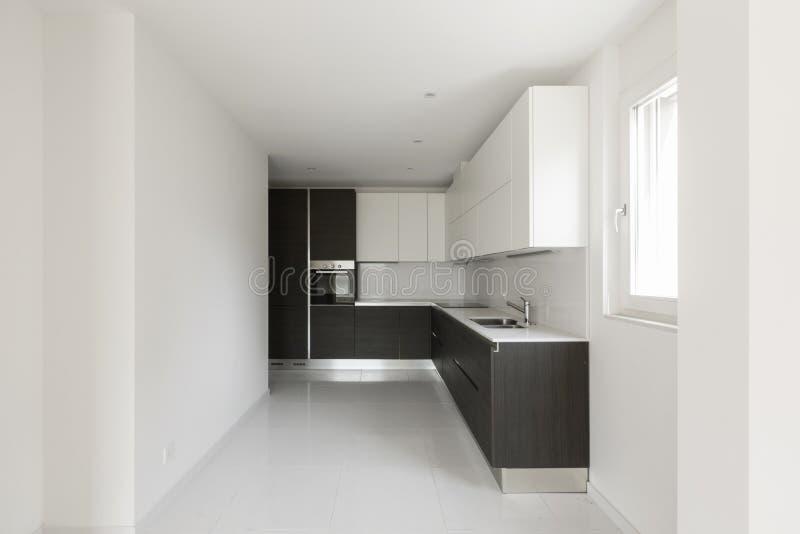 Cocina mínima oscura en un apartamento moderno foto de archivo libre de regalías