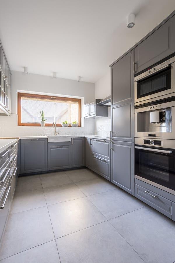 Cocina moderna con muebles grises imagen de archivo libre de regalías