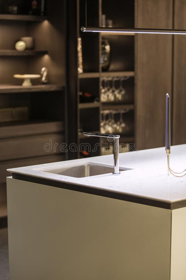 Cocina moderna, el golpecito de agua y fregadero de cocina Isla de cocina con un golpecito y un worktop blanco de mármol foto de archivo