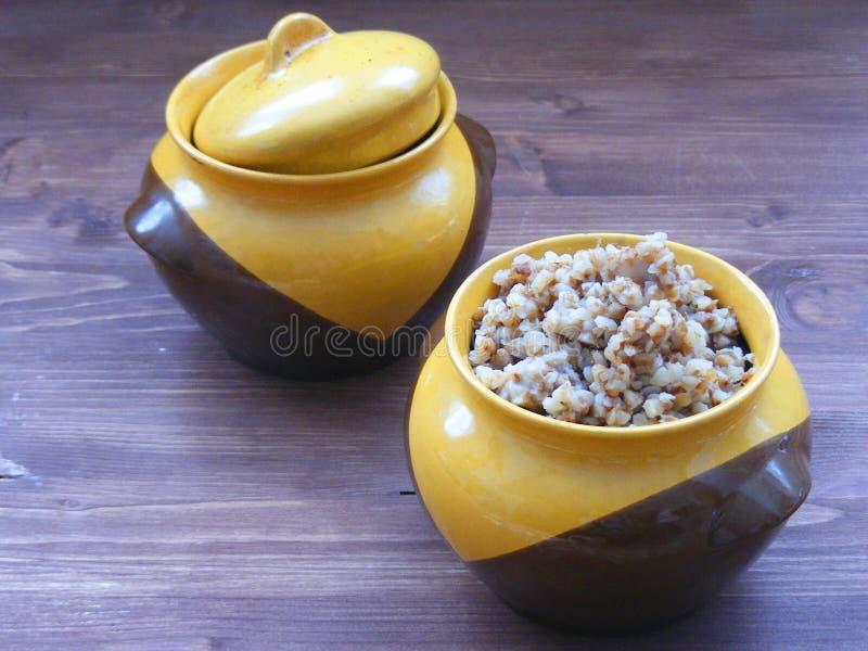 Cocina rústica tradicional rusa y bielorrusa: Avenas mondadas de alforfón en un cuenco de cerámica del vintage en la tabla de mad foto de archivo libre de regalías