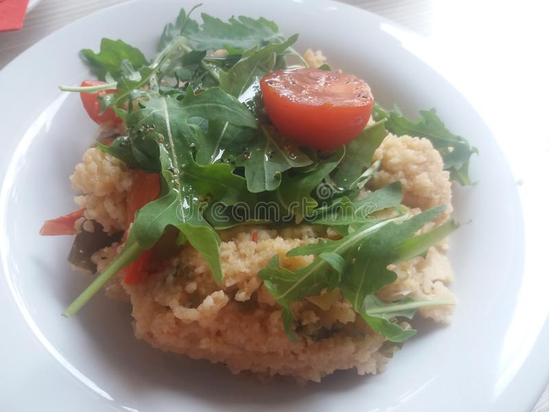 Cocina sana - cuscús con los tomates y el arugula frescos imagen de archivo libre de regalías