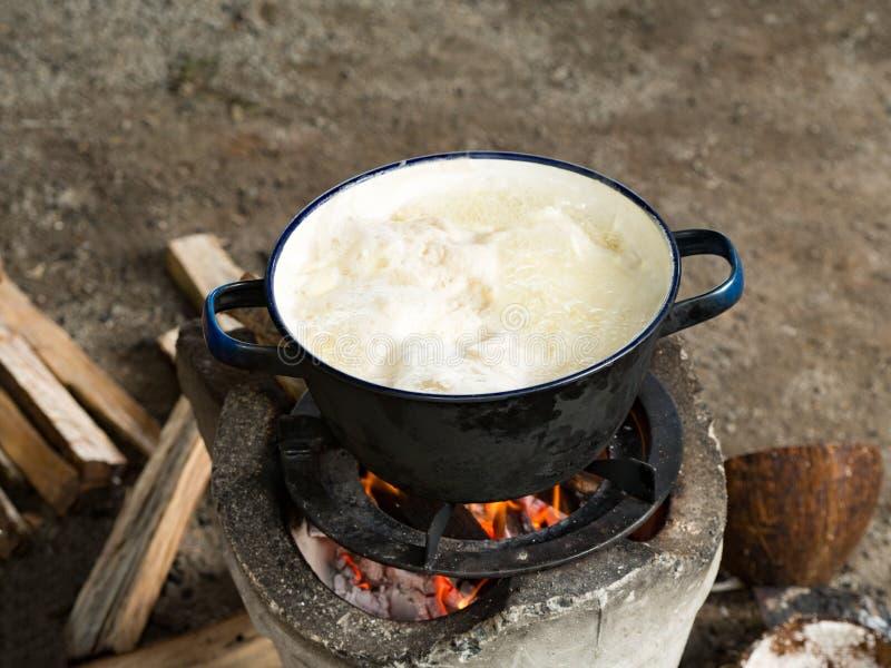 Cocina tailandesa tradicional local Usando la estufa para cocinar por la ebullición en pote en hoguera con las llamas y la leña a fotos de archivo