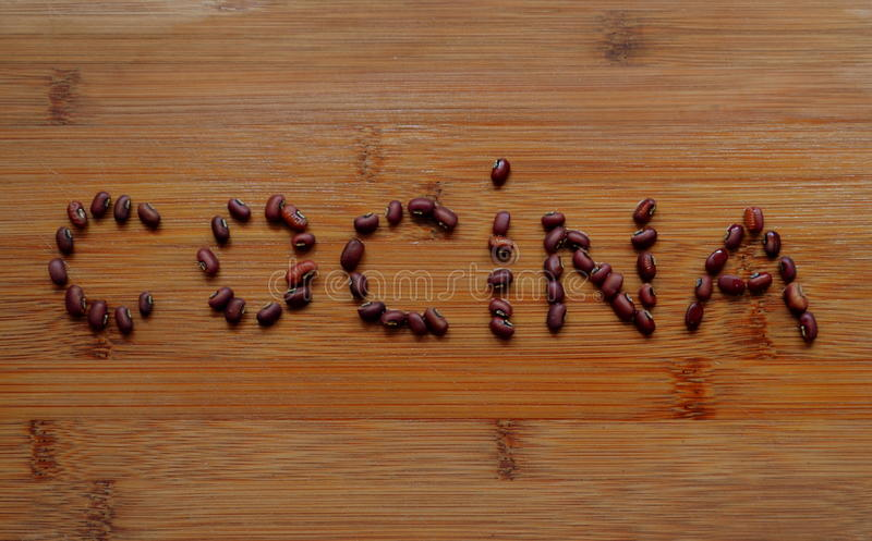 Cocina title with Azuki beans. Spanish word in wood background stock images