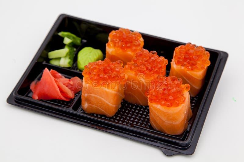 Cocina tradicional japonesa, rollos confeccionados y sushi en el paquete, en un fondo blanco fotografía de archivo