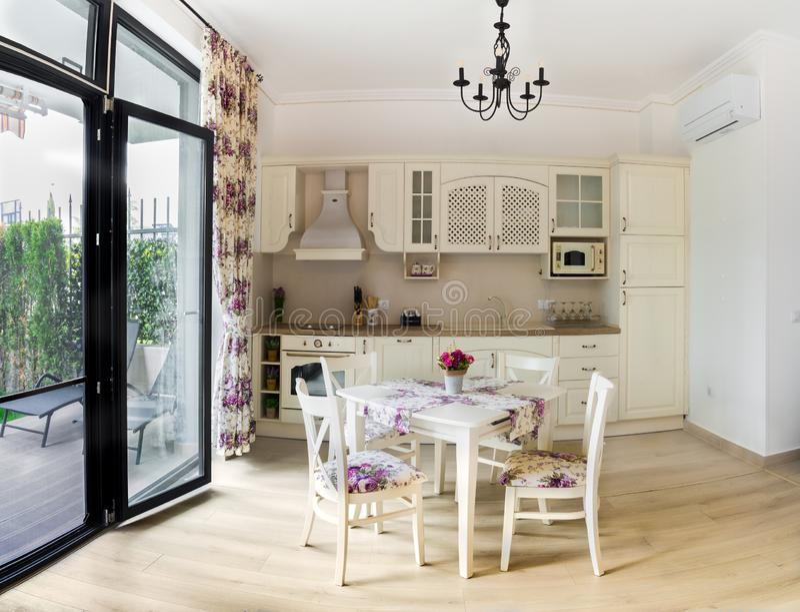 Cocina y gabinetes y tabla con las sillas imagen de archivo libre de regalías