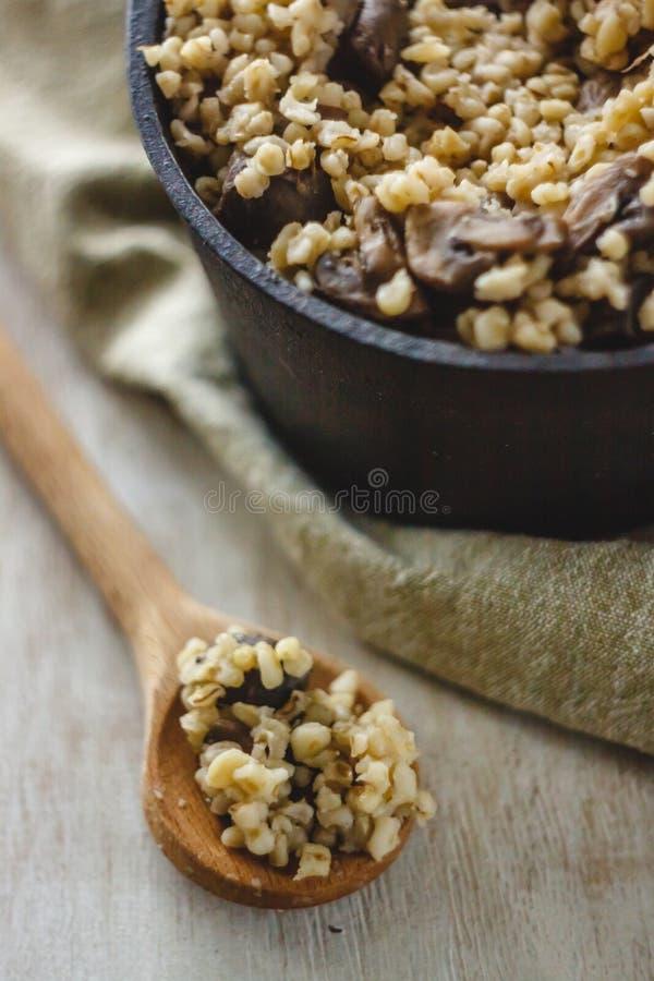 Cocinado para el pote de gachas de avena del bulgur con las setas El concepto de comida simple y sana sana apropiada foto de archivo