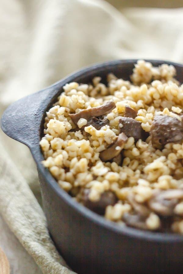 Cocinado para el pote de gachas de avena del bulgur con las setas El concepto de comida simple y sana sana apropiada imagen de archivo