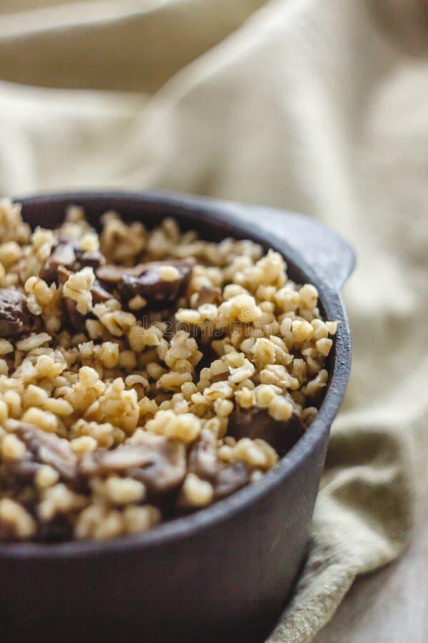 Cocinado para el pote de gachas de avena del bulgur con las setas El concepto de comida simple y sana sana apropiada fotos de archivo libres de regalías