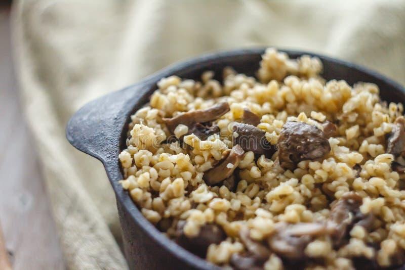 Cocinado para el pote de gachas de avena del bulgur con las setas El concepto de comida simple y sana sana apropiada imagenes de archivo