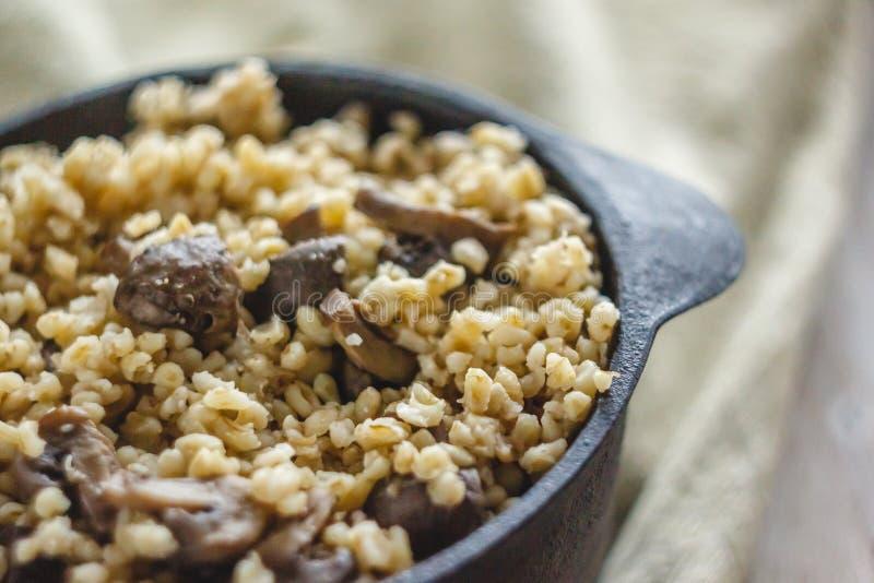 Cocinado para el pote de gachas de avena del bulgur con las setas El concepto de comida simple y sana sana apropiada imágenes de archivo libres de regalías