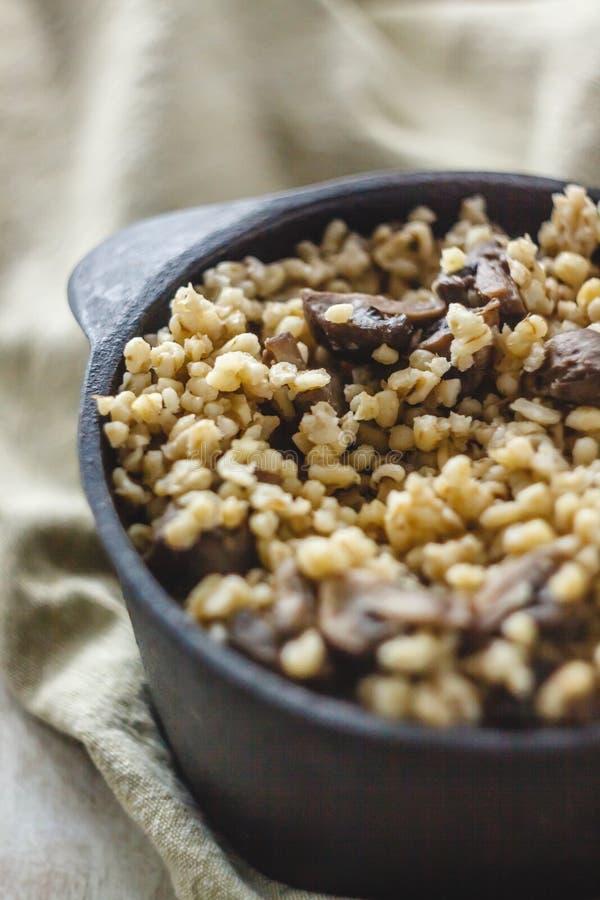 Cocinado para el pote de gachas de avena del bulgur con las setas El concepto de comida simple y sana sana apropiada fotos de archivo
