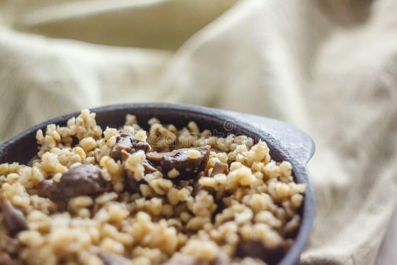 Cocinado para el pote de gachas de avena del bulgur con las setas El concepto de comida simple y sana sana apropiada fotografía de archivo