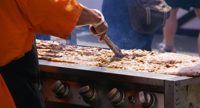 Cocinando kebabs picantes en la feria de la calle, imagen de archivo