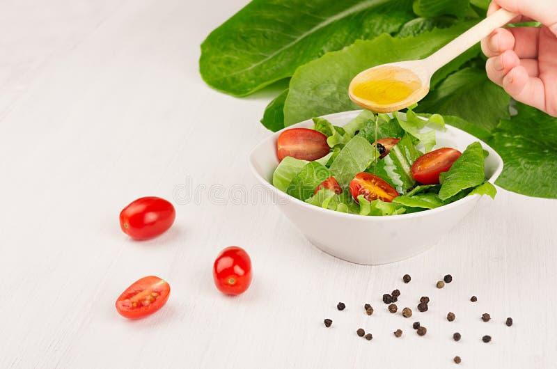 Cocinando la ensalada fresca de la primavera de verdes, las rebanadas del tomate de cereza en el fondo de madera blanco, copian e fotos de archivo libres de regalías