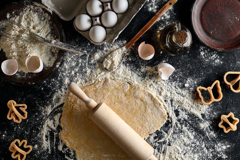 Cocinando la pasta para las galletas, la mantequilla, huevos, cocinando el equipo, flour en una tabla negra Visión superior con e imágenes de archivo libres de regalías