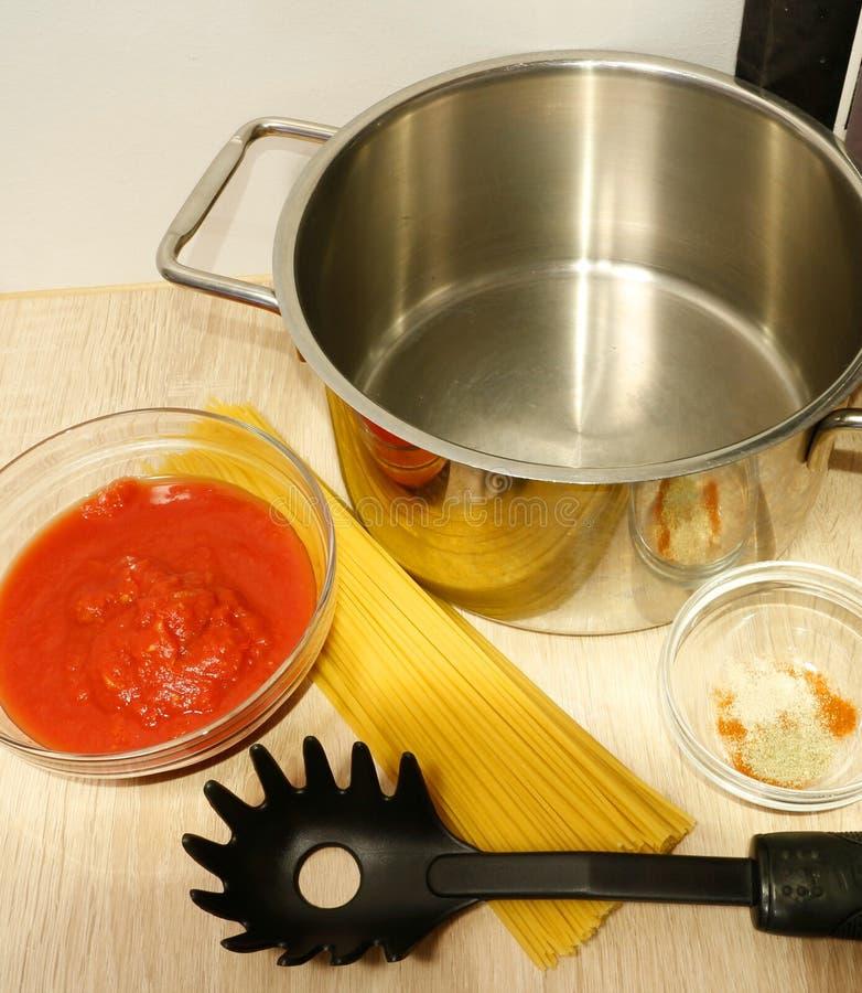 Cocinando la preparación para cocinar la salsa de los espaguetis y de tomate imagen de archivo