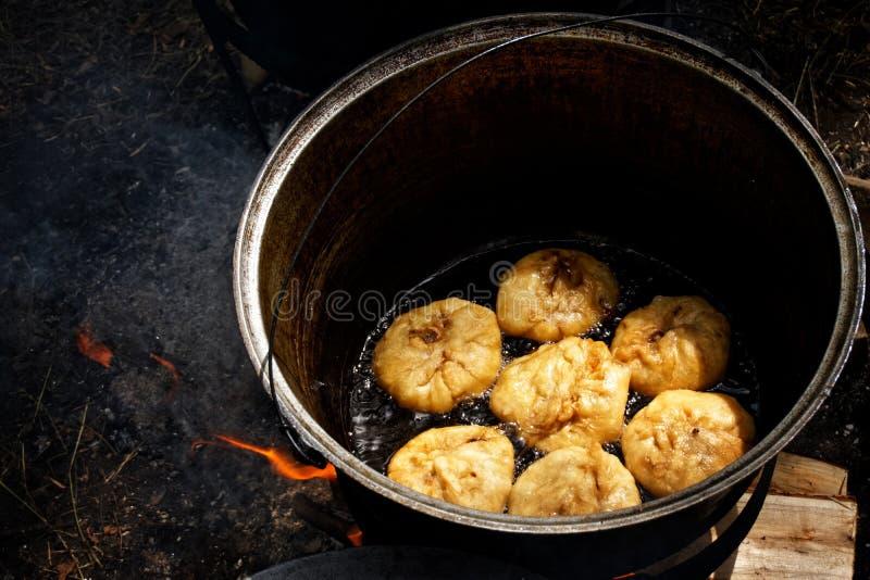 Cocinando a un ruso nacional, plato bashkir, tártaro - belyashes en naturaleza, en una caldera en un fuego abierto fotos de archivo libres de regalías