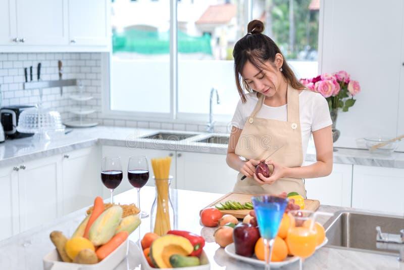 Cocinar al ama de casa asiática de la mujer en la cocina que hace la comida sana fotografía de archivo libre de regalías