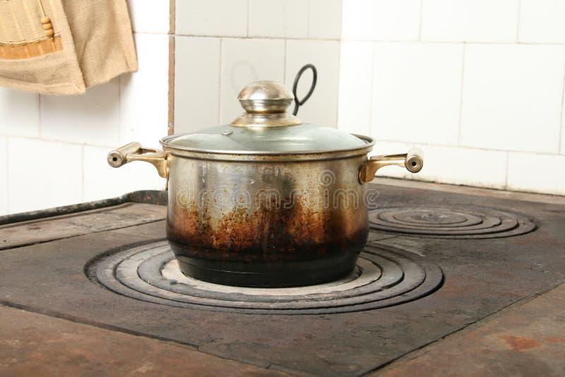 Cocinar el crisol en estufa de cocina vieja imagenes de archivo