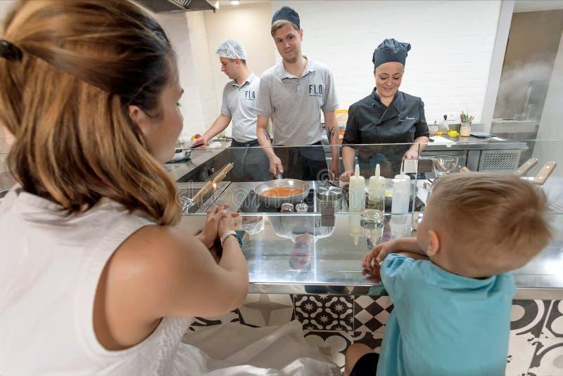 Cocinar el equipo y al cocinero que hacen la comida en la cocina abierta para los niños y las familias dentro del restaurante imagen de archivo